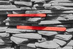 Δύο κόκκινες πέτρες μεταξύ των γκρίζων πετρών Οι γκρίζες πέτρες συσσωρεύονται επάνω Στοκ φωτογραφία με δικαίωμα ελεύθερης χρήσης