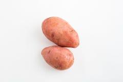 Δύο κόκκινες πατάτες σε ένα άσπρο υπόβαθρο Στοκ εικόνα με δικαίωμα ελεύθερης χρήσης