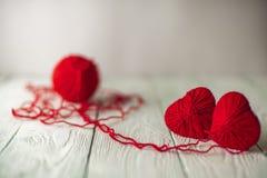 Δύο κόκκινες πλεκτές καρδιές και μια σφαίρα του νήματος Στοκ Φωτογραφία