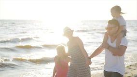 Δύο κόρες και ευτυχείς μητέρα και πατέρας που περπατούν μαζί γύρω από τα χέρια εκμετάλλευσης παραλιών κατά τη διάρκεια των θερινώ απόθεμα βίντεο