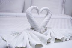 Δύο κύκνοι φιαγμένοι από διαμόρφωση πετσετών μοιάζουν με τη μορφή καρδιών στο κρεβάτι Στοκ Εικόνες