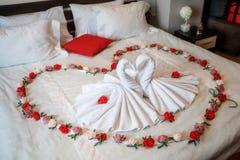 Δύο κύκνοι φιαγμένοι από πετσέτες που διαμορφώνουν τη μορφή καρδιών στο κρεβάτι Στοκ Φωτογραφίες