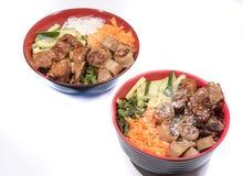Δύο κύπελλα του κουλουριού του BO βόειου κρέατος με τη σαλάτα, πλευρά χοιρινού κρέατος, φρέσκα χορτάρια Στοκ Εικόνα