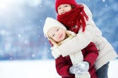Δύο λατρευτά μικρά κορίτσια που έχουν τη διασκέδαση μαζί στο όμορφο χειμερινό πάρκο Όμορφες αδελφές που παίζουν σε ένα χιόνι Στοκ φωτογραφίες με δικαίωμα ελεύθερης χρήσης