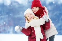 Δύο λατρευτά μικρά κορίτσια που έχουν τη διασκέδαση μαζί στο όμορφο χειμερινό πάρκο Όμορφες αδελφές που παίζουν σε ένα χιόνι Στοκ Φωτογραφίες