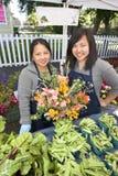 Δύο λουλούδια εκμετάλλευσης κοριτσιών - κατακόρυφος Στοκ Εικόνες