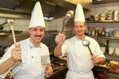 Δύο μάγειρες με τα κουτάλια και κουτάλες σε τους χέρια Στοκ Φωτογραφίες