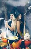Δύο μάγισσες με μια σκούπα, που βάφεται Στοκ Φωτογραφία