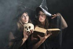 Δύο μάγισσες που προφέρουν τους μαγικούς τύπους Στοκ εικόνα με δικαίωμα ελεύθερης χρήσης