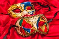 Δύο μάσκες της Mardi Gras στο κόκκινο μετάξι Στοκ Εικόνες