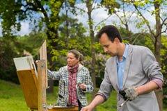 Δύο μέσης ηλικίας επίμονοι ζωγράφοι κατά τη διάρκεια ενός outdo κατηγορίας τέχνης Στοκ Φωτογραφίες