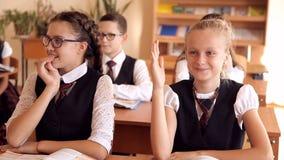 Δύο μαθήτριες σε ομοιόμορφο στο γραφείο της το ένα τραβά τις άλλες απαντήσεις χεριών η ερώτηση απόθεμα βίντεο