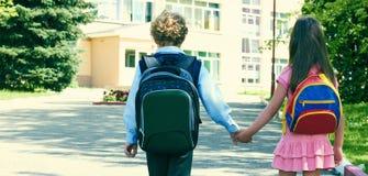 Δύο μαθητές του δημοτικού σχολείου πηγαίνουν χέρι-χέρι Αγόρι και κορίτσι με τις σχολικές τσάντες πίσω από την πλάτη Δύο μαθητές α Στοκ Φωτογραφία