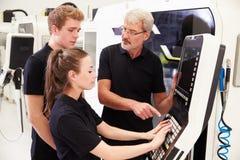 Δύο μαθητευόμενοι που συνεργάζονται με το μηχανικό CNC στα μηχανήματα Στοκ Εικόνα