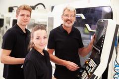 Δύο μαθητευόμενοι που συνεργάζονται με το μηχανικό CNC στα μηχανήματα Στοκ εικόνες με δικαίωμα ελεύθερης χρήσης