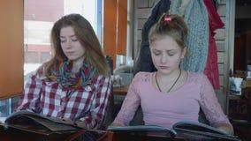 Δύο μακρυμάλλη blondes στις επιλογές μελέτης καφέδων εξετάζουν έπειτα το ένα το άλλο και το χαμόγελο απόθεμα βίντεο