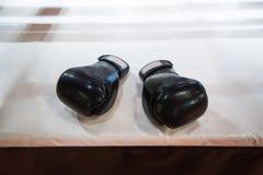 Δύο μαύρα εγκιβωτίζοντας γάντια βρίσκονται στο εγκιβωτίζοντας δαχτυλίδι στο λευκό Το sha Στοκ εικόνες με δικαίωμα ελεύθερης χρήσης