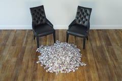 Δύο μαύρες έδρες στο μινιμαλιστικό εσωτερικό με το σωρό των χρημάτων Στοκ Εικόνα