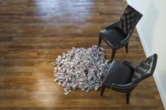 Δύο μαύρες έδρες στο μινιμαλιστικό εσωτερικό με το σωρό των χρημάτων Στοκ φωτογραφία με δικαίωμα ελεύθερης χρήσης