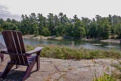 Δύο μαύρες καρέκλες Muskoka που κάθονται σε μια ξύλινη αποβάθρα που αντιμετωπίζει μια λίμνη Πέρα από το ήρεμο νερό είναι ένα άσπρ στοκ φωτογραφία
