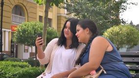Δύο μεγάλα συμπαθητικά καυκάσια κορίτσια που μιλούν την ψύχρα και που κρατούν το smartphone στον πάγκο υπαίθριο φιλμ μικρού μήκους
