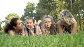 Δύο μητέρες και δύο μικρές κόρες βρίσκονται στην πράσινη χλόη στο πάρκο στο ηλιοβασίλεμα, το παιχνίδι και το φίλημα r r απόθεμα βίντεο
