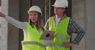 Δύο μηχανικοί ένας άνδρας και μια γυναίκα με έναν υπολογιστή ταμπλετών σε ένα εργοτάξιο οικοδομής καταδικάζουν το σχέδιο κατασκευ απόθεμα βίντεο