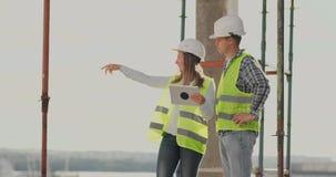 Δύο μηχανικοί ένας άνδρας και μια γυναίκα με έναν υπολογιστή ταμπλετών σε ένα εργοτάξιο οικοδομής καταδικάζουν το σχέδιο κατασκευ φιλμ μικρού μήκους