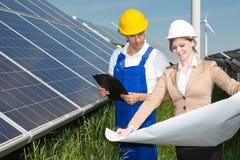 Δύο μηχανικοί εξετάζουν το σχέδιο κατασκευής των ηλιακών πλαισίων στοκ φωτογραφίες