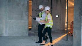 Δύο μηχανικοί που μιλούν εργαζόμενοι σε ένα εργοτάξιο οικοδομής, πλάγια όψη απόθεμα βίντεο