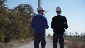 Δύο μηχανικοί που περπατούν προς το αιολικό πάρκο φιλμ μικρού μήκους