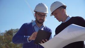 Δύο μηχανικοί που συζητούν ένα σχεδιάγραμμα φιλμ μικρού μήκους