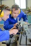 Δύο μηχανικοί που τα καλύμματα αυτιών που εξετάζουν τα μηχανήματα Στοκ Εικόνες