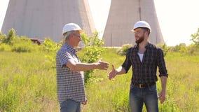 Δύο μηχανικοί στα σκληρά καπέλα που τινάζουν τα χέρια απόθεμα βίντεο