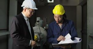 Δύο μηχανικοί συζητούν για τα κουνήματα σχεδιαγραμμάτων και χεριών, έννοια για την επιχειρησιακή ομιλία απόθεμα βίντεο