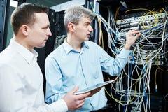 Δύο μηχανικοί υποστήριξης δικτύων που διαχειρίζονται στο δωμάτιο κεντρικών υπολογιστών Στοκ Εικόνες