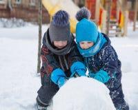 Δύο μικρά αγόρια κυλούν τη μεγάλη χιονιά Στοκ Εικόνες