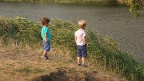 Δύο μικρά αγόρια ρίχνουν τις πέτρες στη λίμνη απόθεμα βίντεο