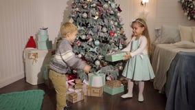 Δύο μικρά ανοικτά δώρα παιδιών κοντά στο χριστουγεννιάτικο δέντρο απόθεμα βίντεο