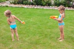 Δύο μικρά λατρευτά κορίτσια που παίζουν με τα πυροβόλα όπλα νερού Στοκ Εικόνες