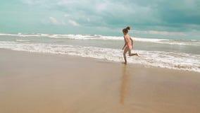 Δύο μικρά γοητευτικά κορίτσια τρέχουν κατά μήκος της θάλασσας κατά μήκος των ευτυχών παιδιών ακτών στις διακοπές φιλμ μικρού μήκους