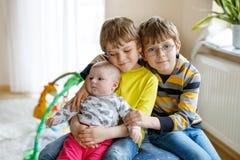 Δύο μικρά ευτυχή αγόρια παιδιών με το νεογέννητο κοριτσάκι, χαριτωμένη αδελφή Στοκ εικόνα με δικαίωμα ελεύθερης χρήσης