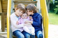 Δύο μικρά ευτυχή αγόρια παιδιών με το νεογέννητο κοριτσάκι, χαριτωμένη αδελφή Στοκ φωτογραφία με δικαίωμα ελεύθερης χρήσης