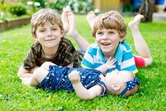 Δύο μικρά ευτυχή αγόρια παιδιών με το νεογέννητο κοριτσάκι, χαριτωμένη αδελφή Στοκ Εικόνες
