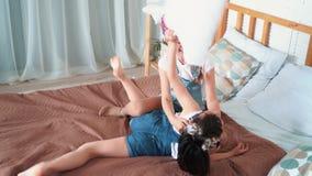 Δύο μικρά ευτυχή κορίτσια παίζουν στο κρεβάτι, τη γαργάλημα μεταξύ τους και το γέλιο, σε αργή κίνηση απόθεμα βίντεο