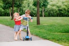 Δύο μικρά καυκάσια προσχολικά παιδιά που παλεύουν στο πάρκο έξω Το αγόρι και το κορίτσι δεν μπορούν να μοιραστούν ένα μηχανικό δί στοκ φωτογραφίες