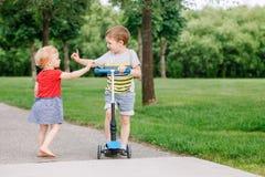 Δύο μικρά καυκάσια προσχολικά παιδιά που παλεύουν στο πάρκο έξω Το αγόρι και το κορίτσι δεν μπορούν να μοιραστούν ένα μηχανικό δί στοκ εικόνες
