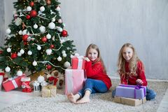 Δύο μικρά κορίτσια ανοίγουν τα δώρα Χριστουγέννων στο νέο σπίτι διακοπών έτους χριστουγεννιάτικων δέντρων στοκ εικόνες με δικαίωμα ελεύθερης χρήσης