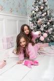 Δύο μικρά κορίτσια γύρω από το χριστουγεννιάτικο δέντρο Στοκ φωτογραφία με δικαίωμα ελεύθερης χρήσης