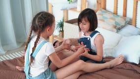 Δύο μικρά κορίτσια κάθονται στο κρεβάτι, παίζουν το ένα με το άλλο, ένα από τα κερδίζει, σε αργή κίνηση απόθεμα βίντεο